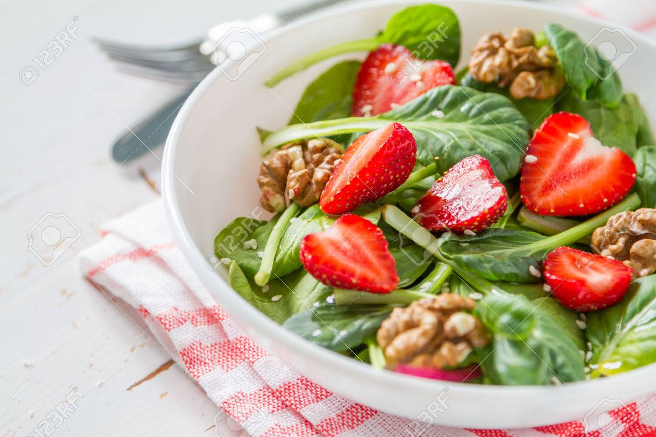 Strawberry salad in white bowl, white wwod background, copy space, closeup Stock Photo - 48447620