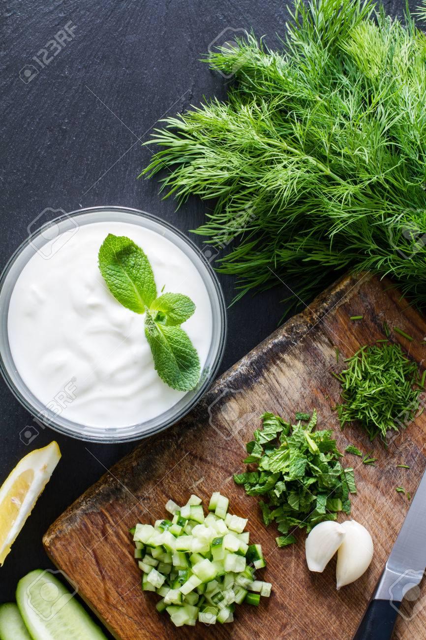 Preparing tzatziki sauce and ingredients, dark stone background, top view Stock Photo - 48450330