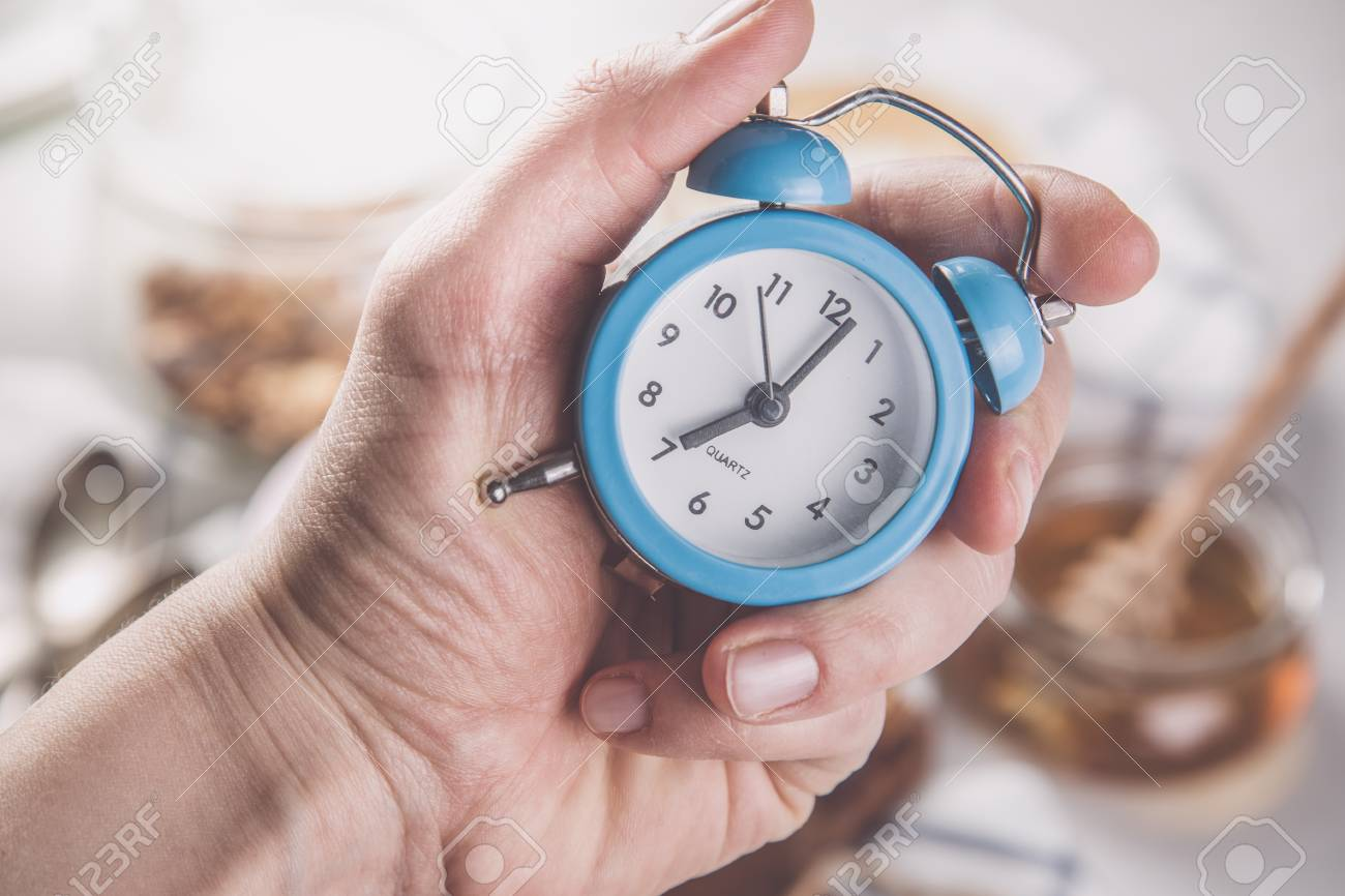 Morning alarm concept - hand with clock Stock Photo - 73363046
