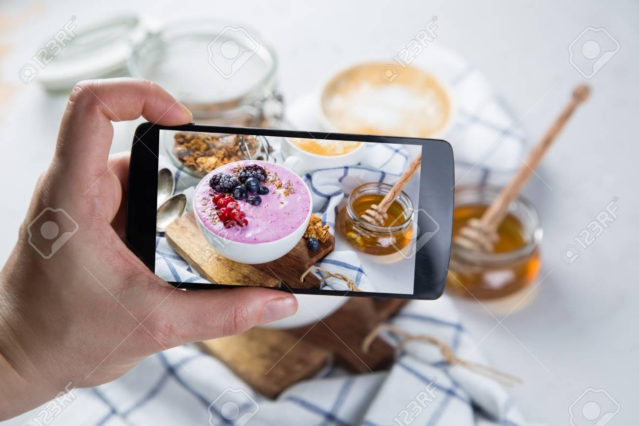 Taking photos of breakfast to phone Stock Photo - 73363050