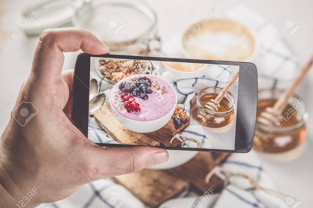 Taking photos of breakfast to phone Stock Photo - 73363051