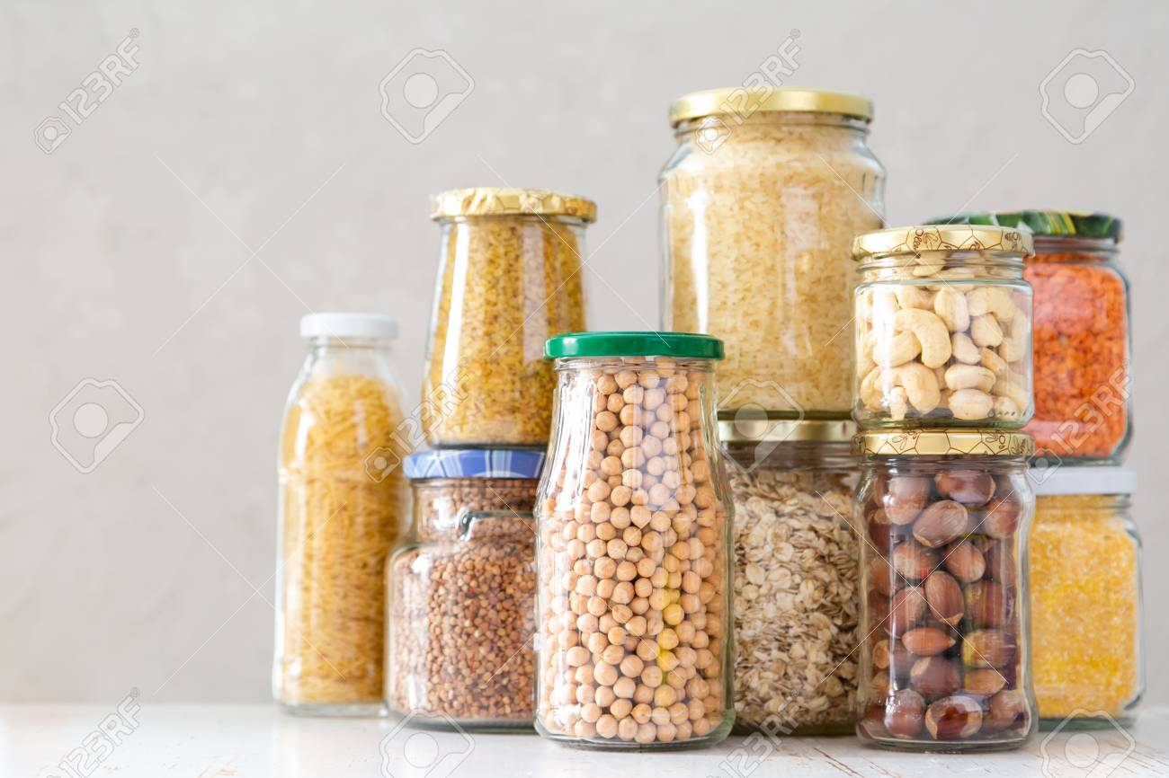 Various uncooked cereals, grains, beans and pasta for healthy cooking in glass jars - 113299442