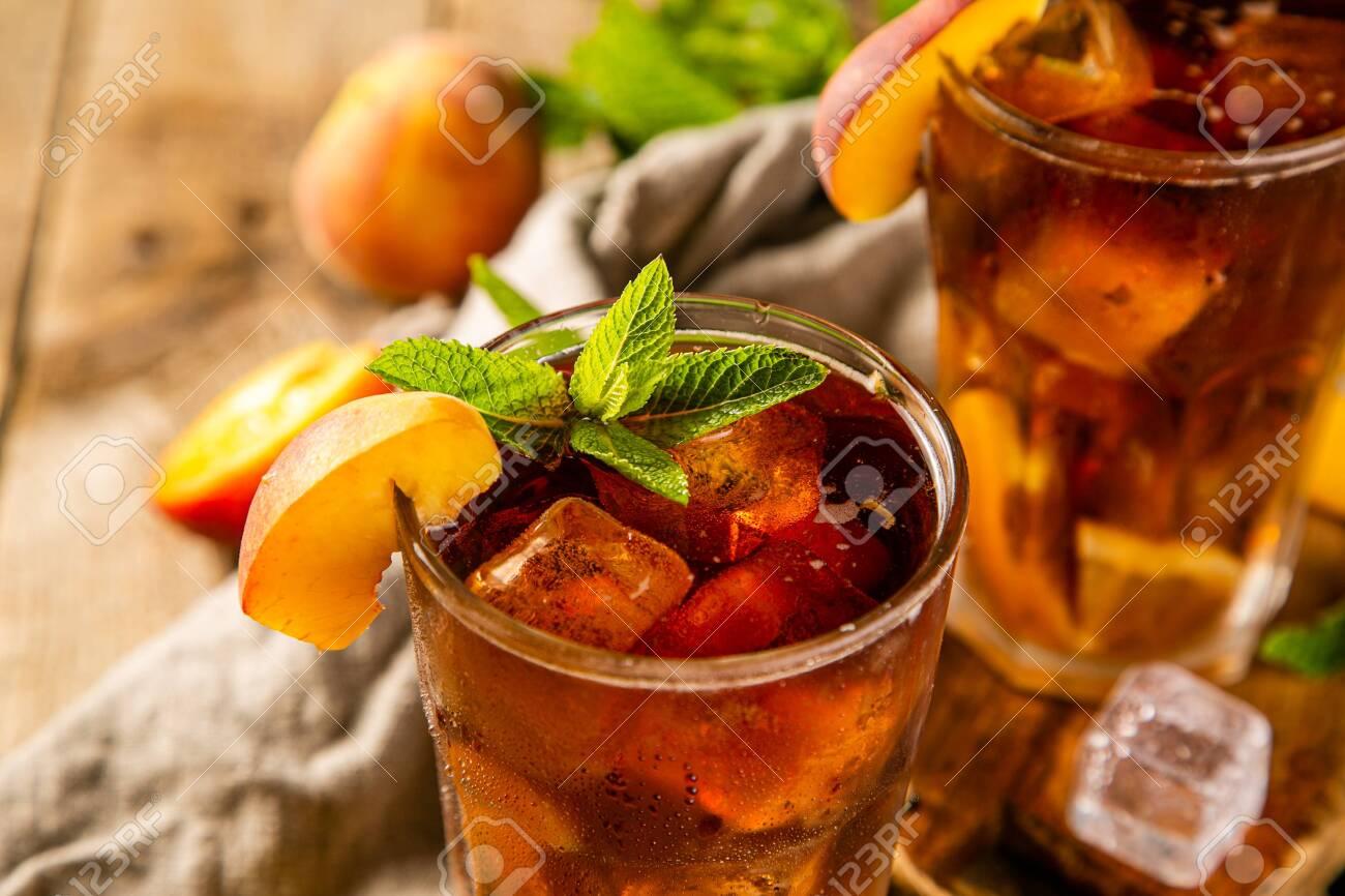 Lemon and peach iced tea on wooden background - 125133054