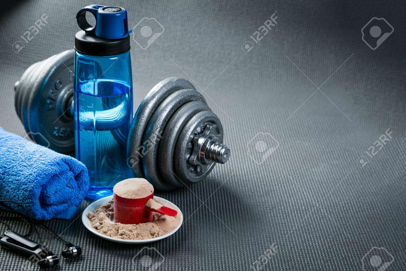 Sport concept - gym supplies on yoga mat background - 164100000