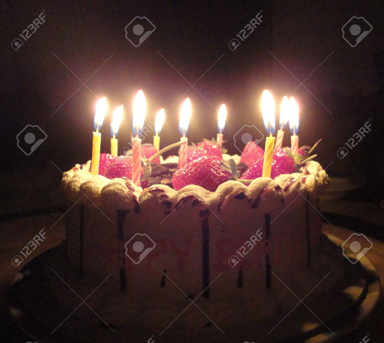 Birthday Cake With Sweet Strawberry And Light Candle In The Dark