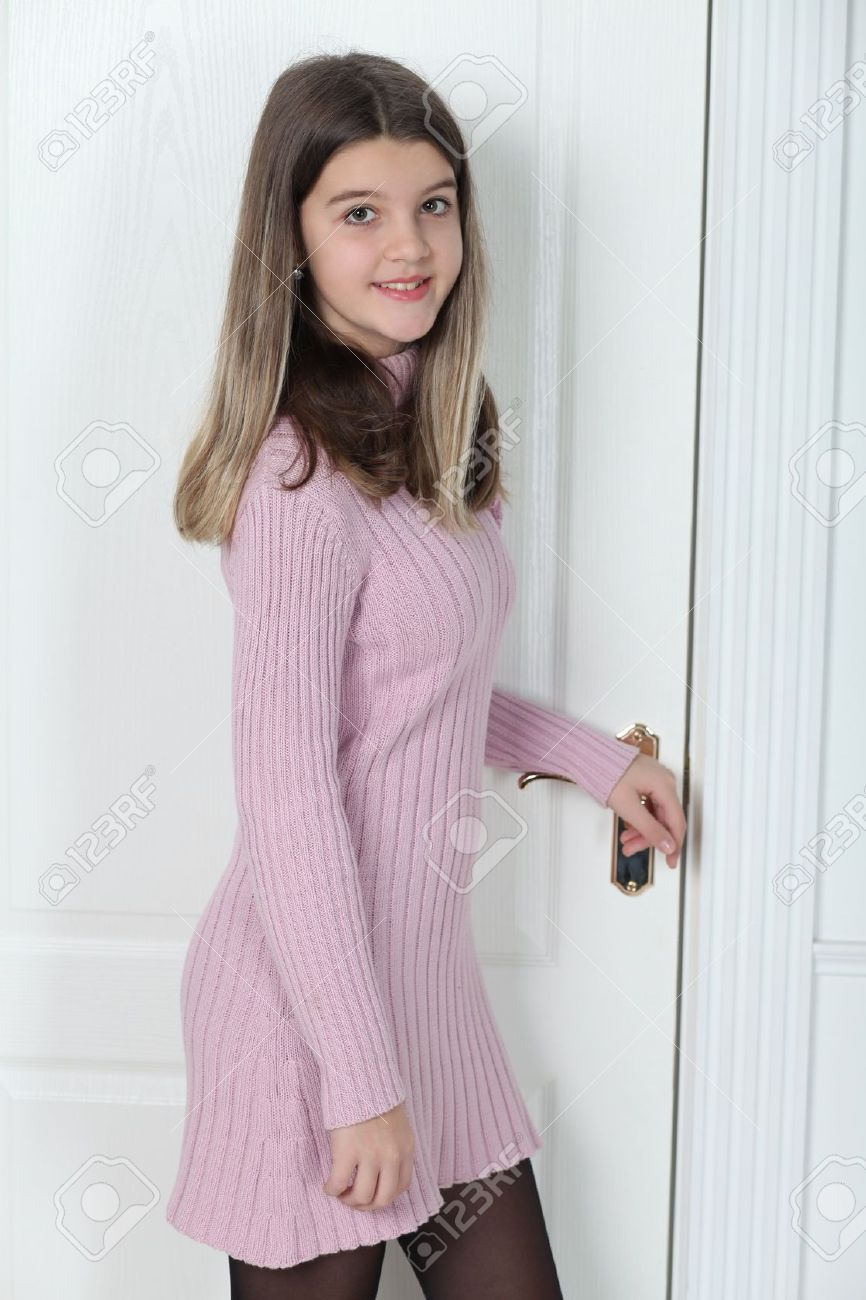 Little girl standing at the white door closed Stock Photo - 16715900