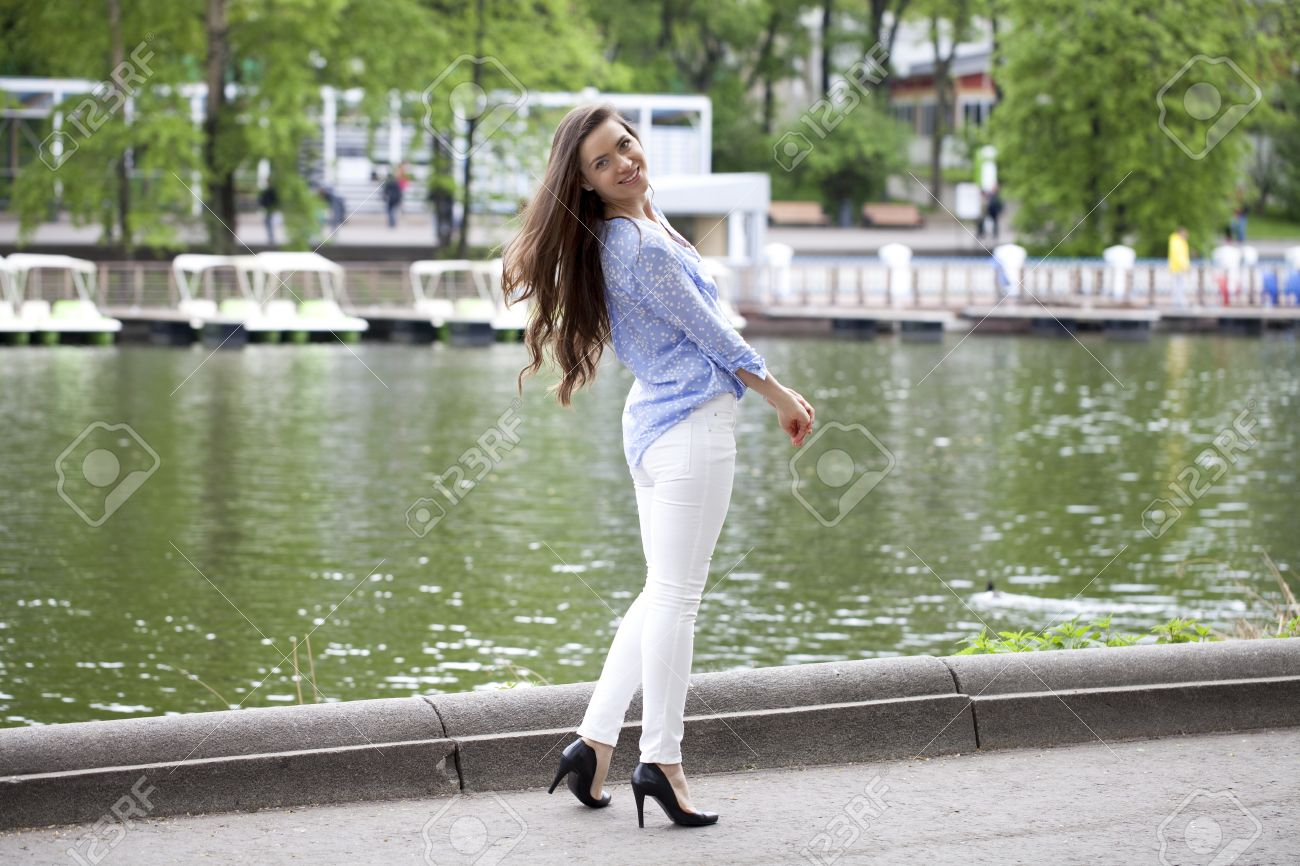 Happy Young Woman In White Pants And A Blue Shirt Walking In ...