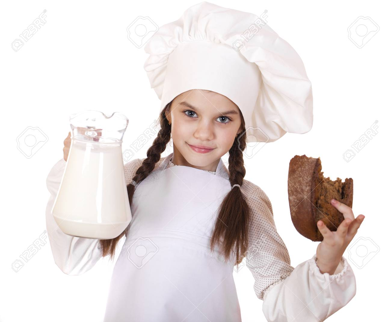 Cooking and people concept little girl in a white apron holding a jug of milk