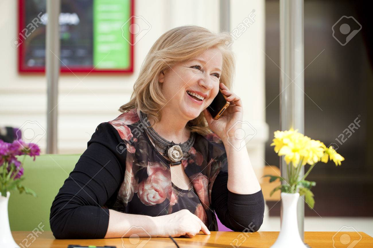 Mature beautiful blonde woman is calling on a cell phone while sitting in a coffee shop Stock Photo - 38701475
