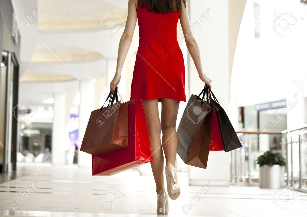 Beautiful young woman in a red dress, holding shopping bags walking in the shop Stock Photo - 39205595