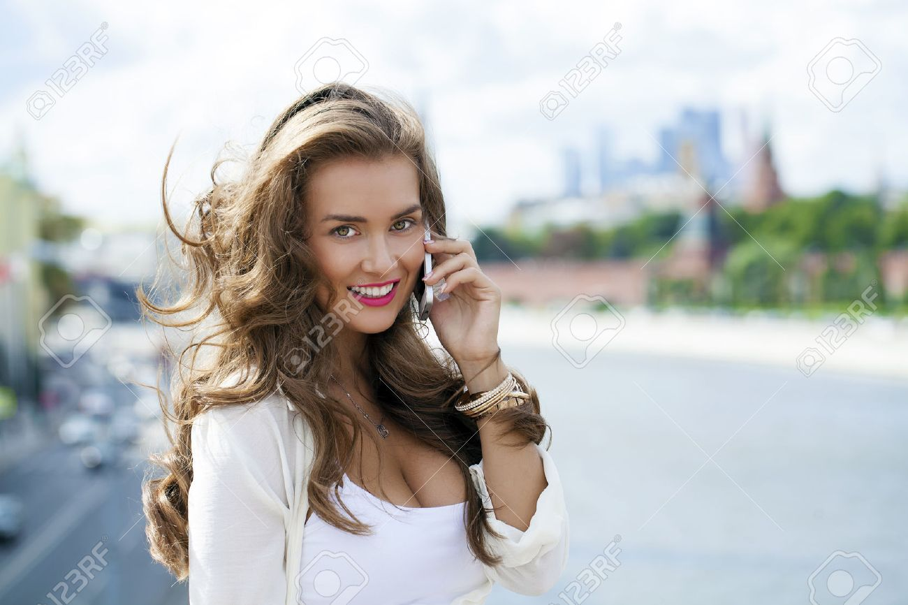 Happy beautiful girl calling by phone in a summer street Stock Photo - 39578087