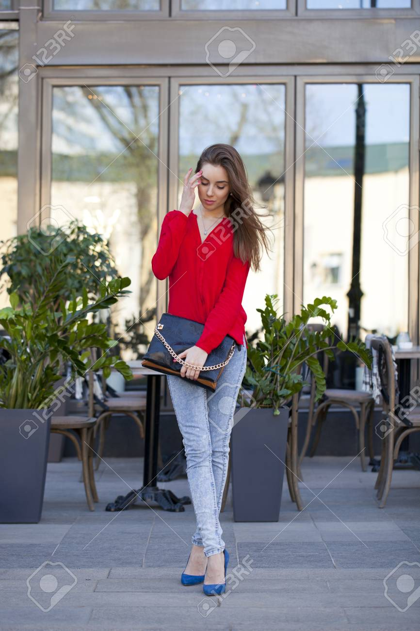 1ba83a050be Portrait in full growth the young beautiful girl in blue jeans and red shirt  on the
