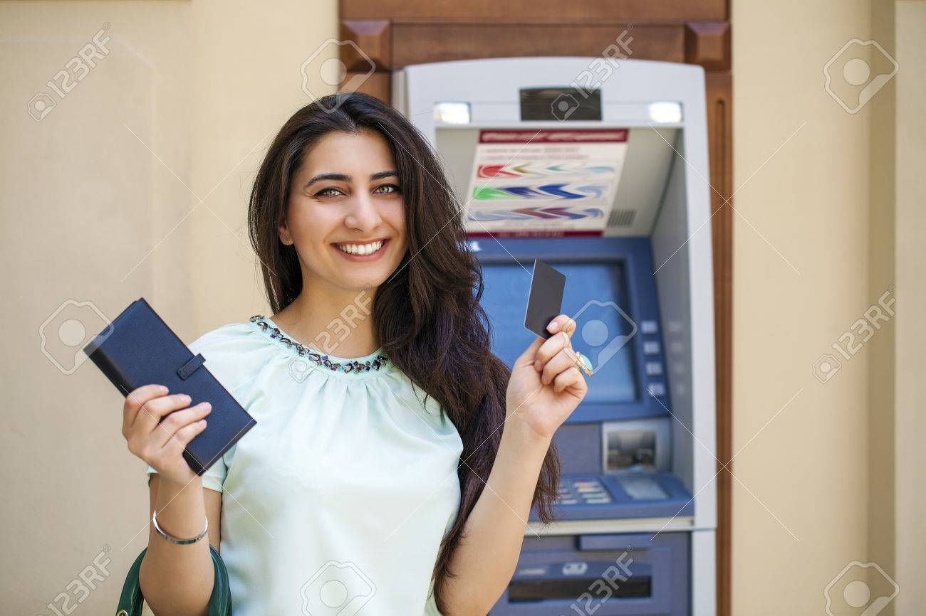 Brunette young lady using an automated teller machine . Woman withdrawing money or checking account balance Stock Photo - 41957357
