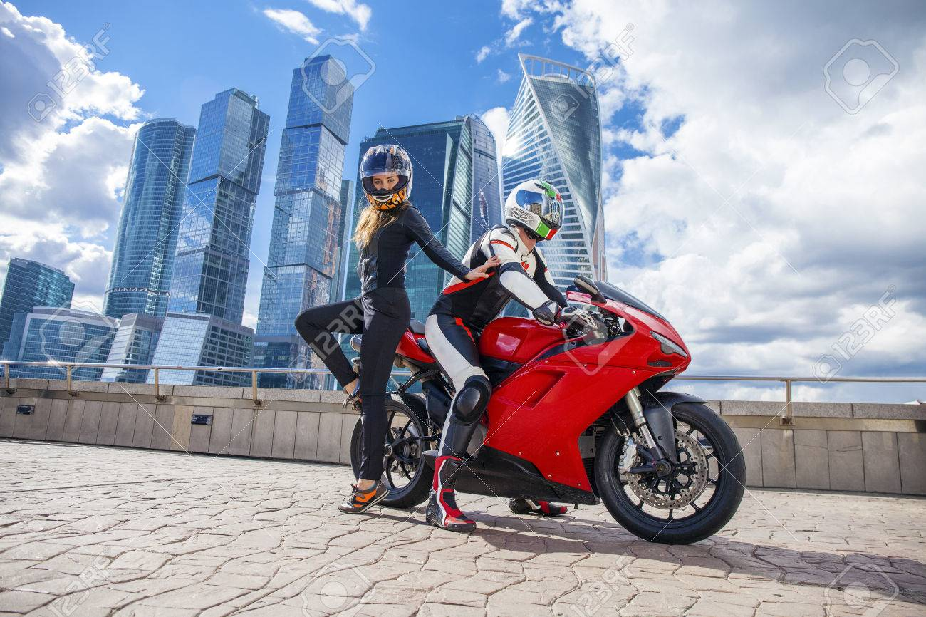Couple In A Suit With A Motorcycle Sport Bike On The Background