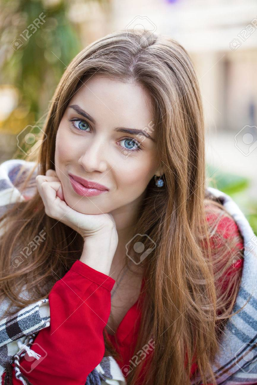 Portrait of a beautiful young woman sitting in a cafe on the street Stock Photo - 44500646