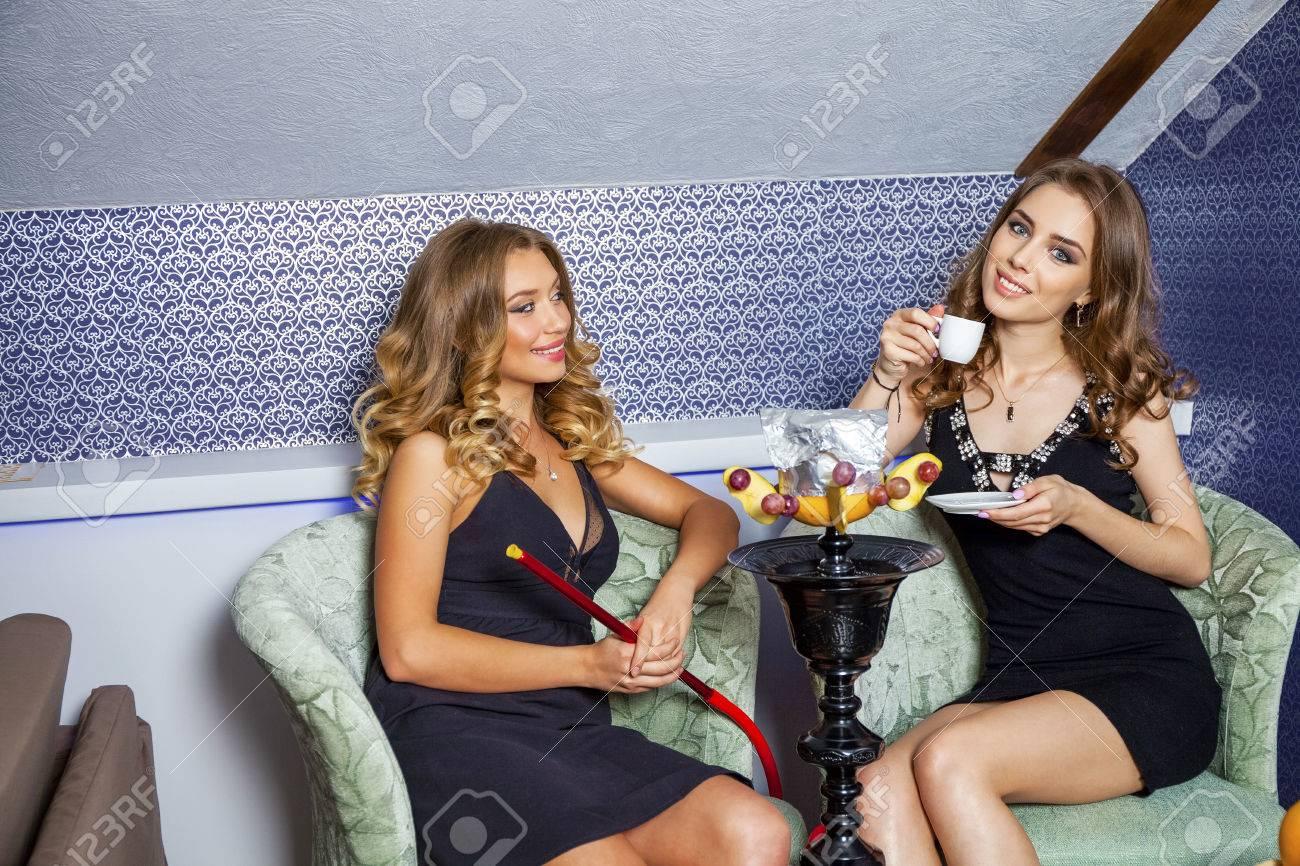 df8d9d7ee985 Archivio Fotografico - Ritratto di bellezza di due giovani donne sexy che  riposano nella sala narghilè