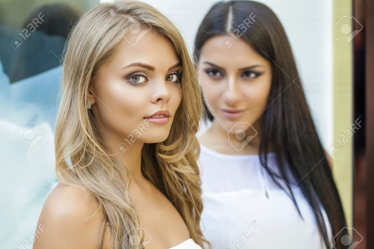 e77da0fb Glamorous portrait of two young beautiful women. Blonde and brunette women,  indoor Stock Photo