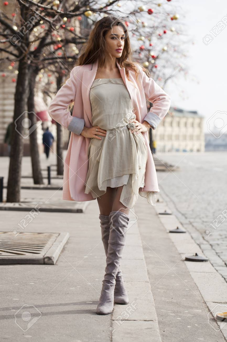 Portrait in full growth, young brunette woman in pink coat - 54126711