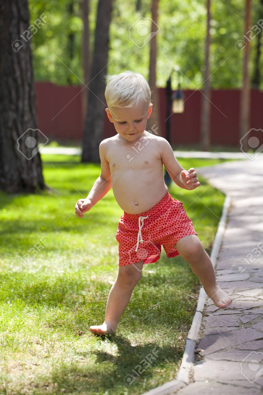 901fabe9a Portrait of blonde baby boy in red shorts walking in summer park Stock  Photo - 55133669