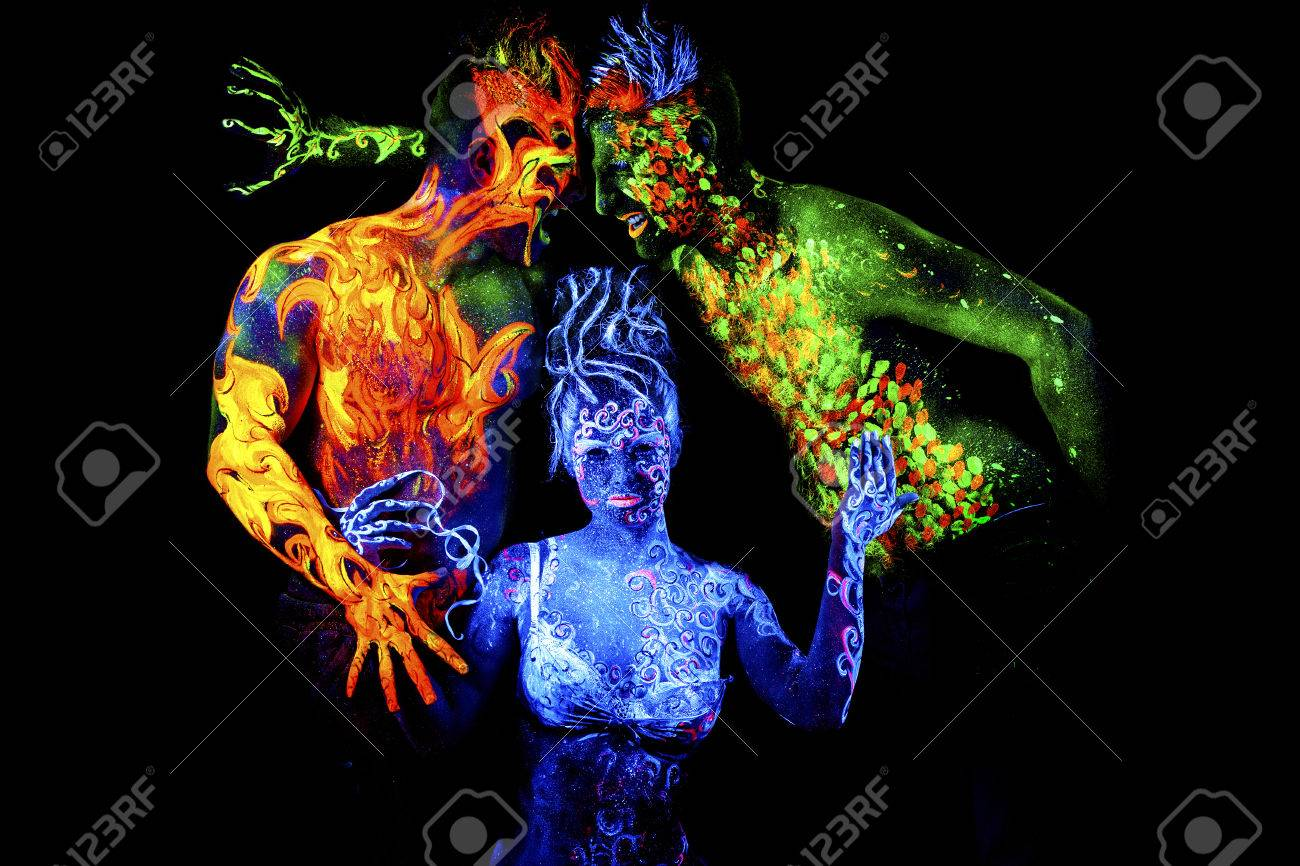 Four Elements Art : Fire land and air. body art glowing in ultraviolet light four