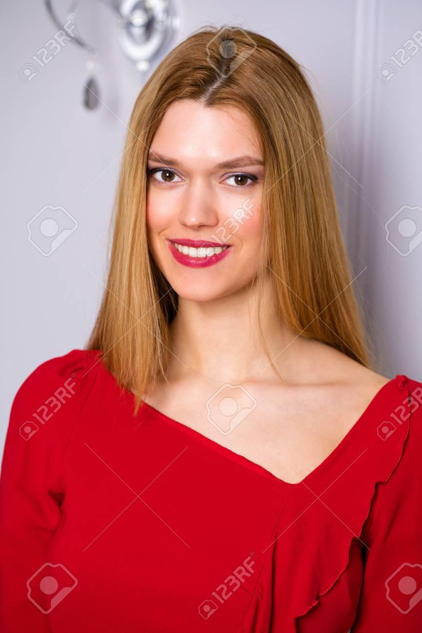 Maquillaje Joven Y Bella Mujer De Vestido Rojo En La Pared Gris Fondo Del Estudio