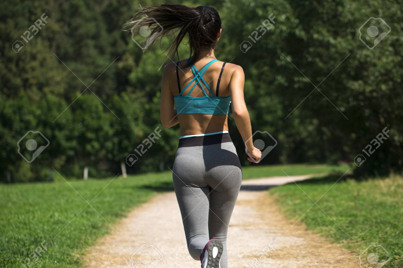 close up sexy ass. athletic woman working out in a meadow, from