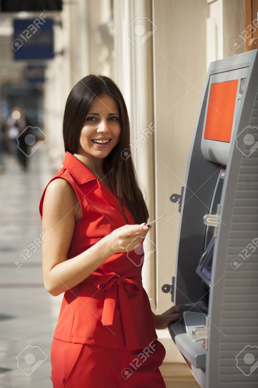 f64f9a16afeb Stock Photo - Young happy brunette woman in red dress withdrawing money  from credit card at ATM
