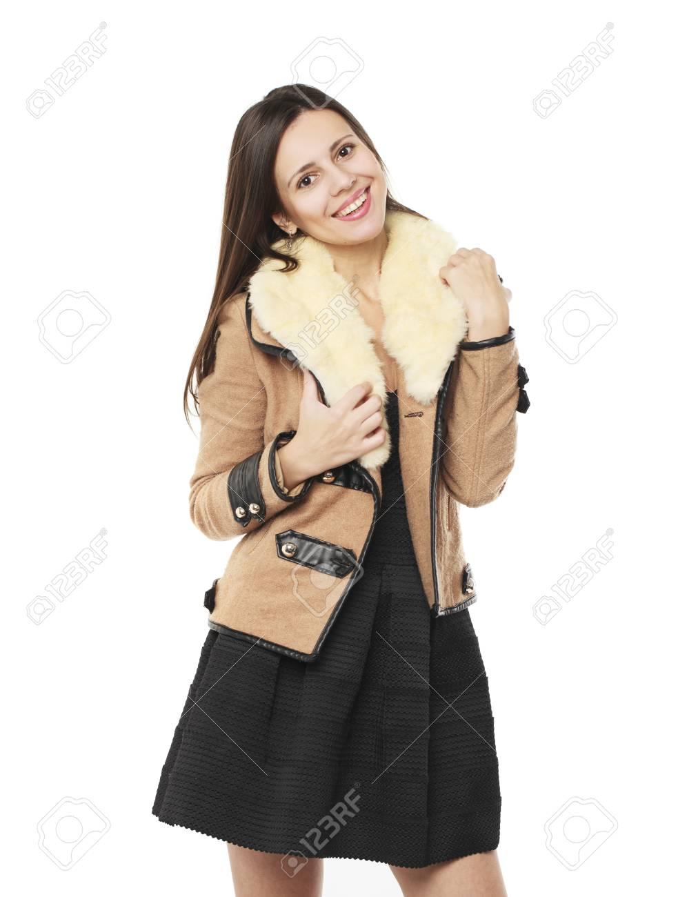 Jeune belle femme brune en élégant manteau beige en peau de mouton, isolé sur fond blanc