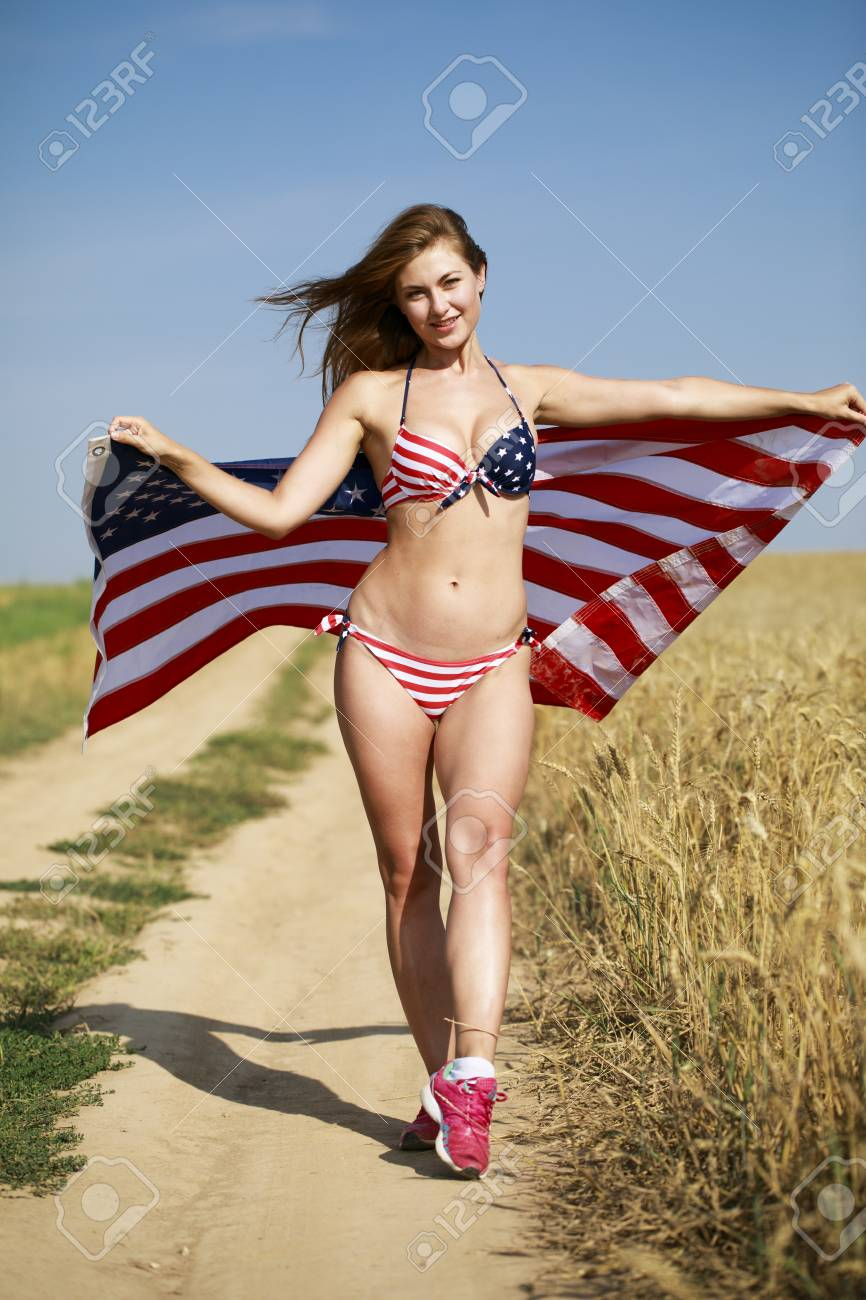 226b7bba3968f Stock Photo - Young beautiful blonde woman in sexy American flag bikini in  a wheat field