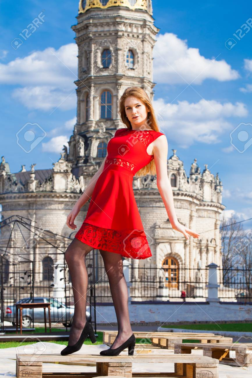 Portrait full length of young beautiful woman in red dress. Znamenskaya  church in manor Dubrovitsy 89b0ff460ce