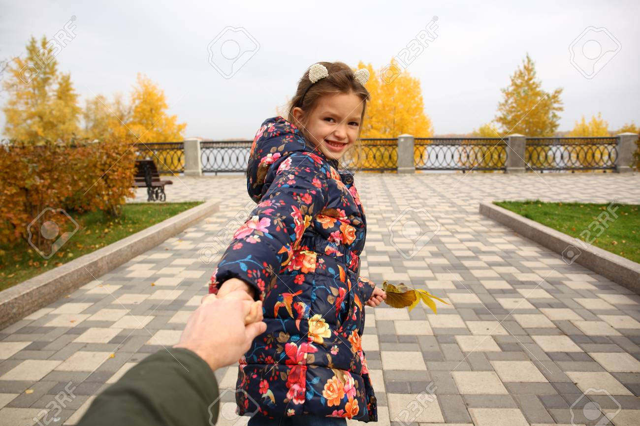 Follow me, Beautiful little girl holds the hand of a father in autumn city park - 110070639