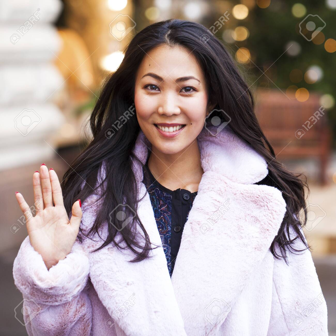 Happy asian woman in winter coat from faux fur, walking on red square, Russia - 123192589