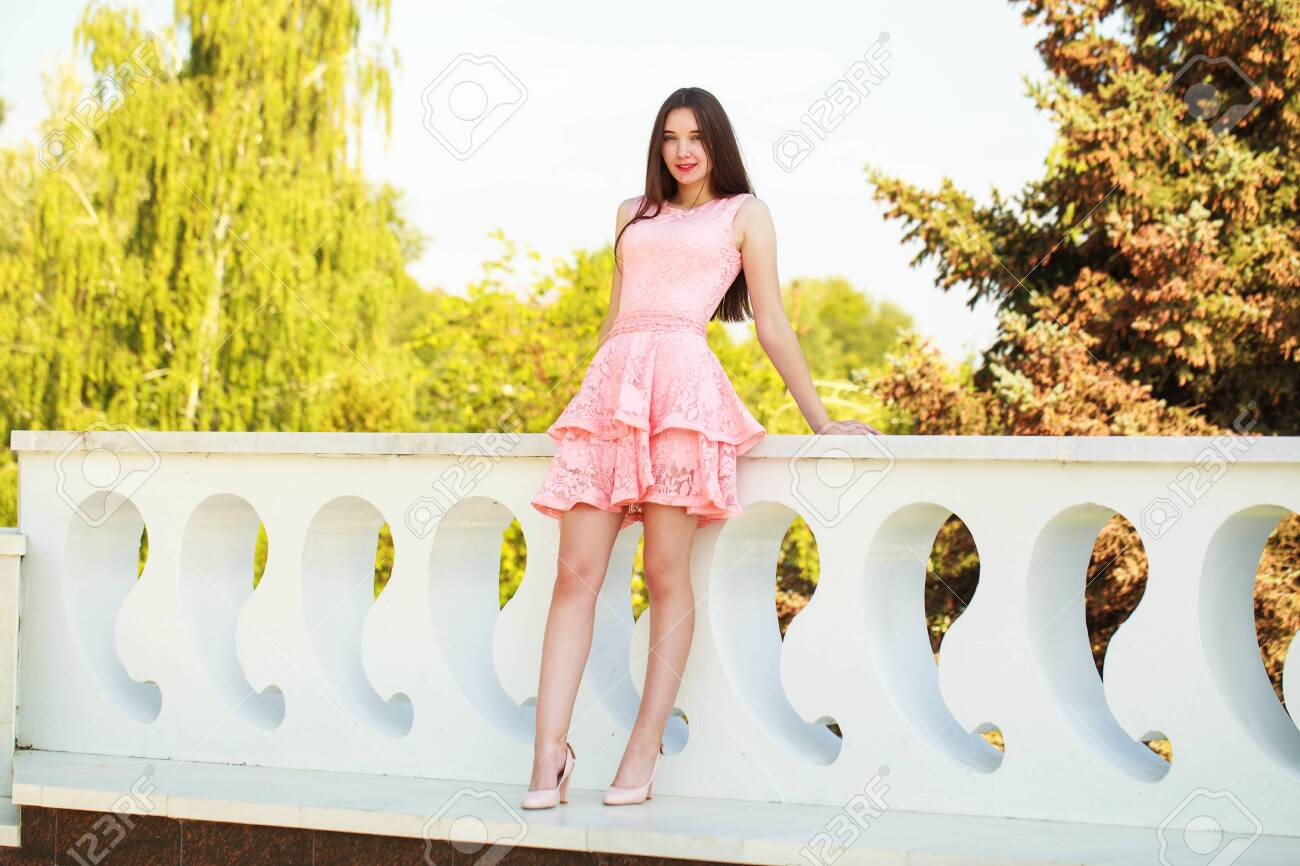 Portrait in full growth, young beautiful brunette woman in a pink dress walking on the street, summer embankment outdoors - 137743026