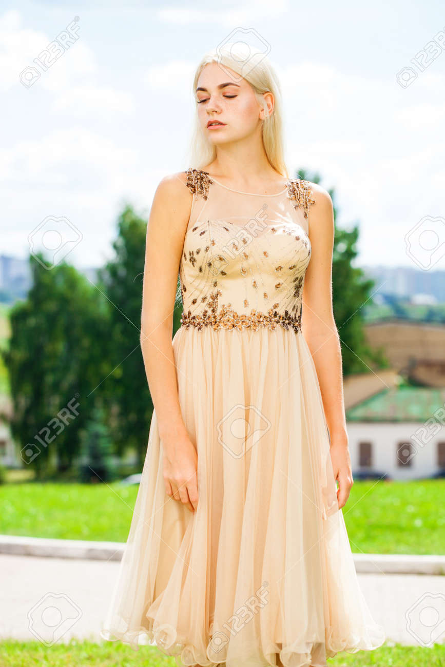 Portrait of a young beautiful blonde woman in beige dress - 154215631