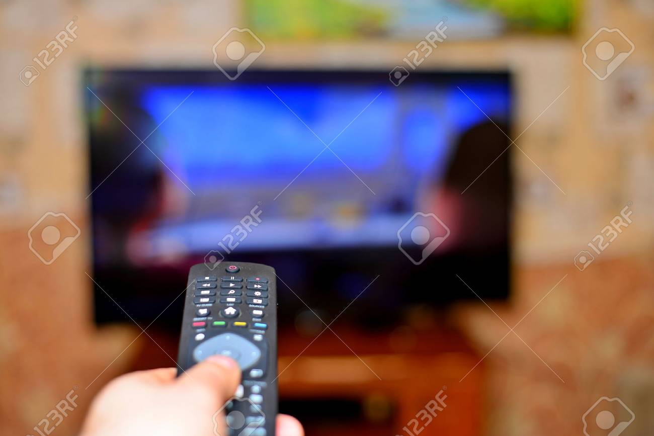 The man with the remote control in hand watching the sports channel and presses the button on the remote control. Remote control in hand closeup. - 93800734