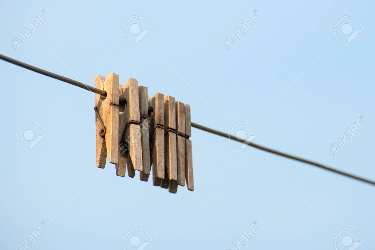 Wooden Clothespins Hanging On A Steel Wire On A Light Background