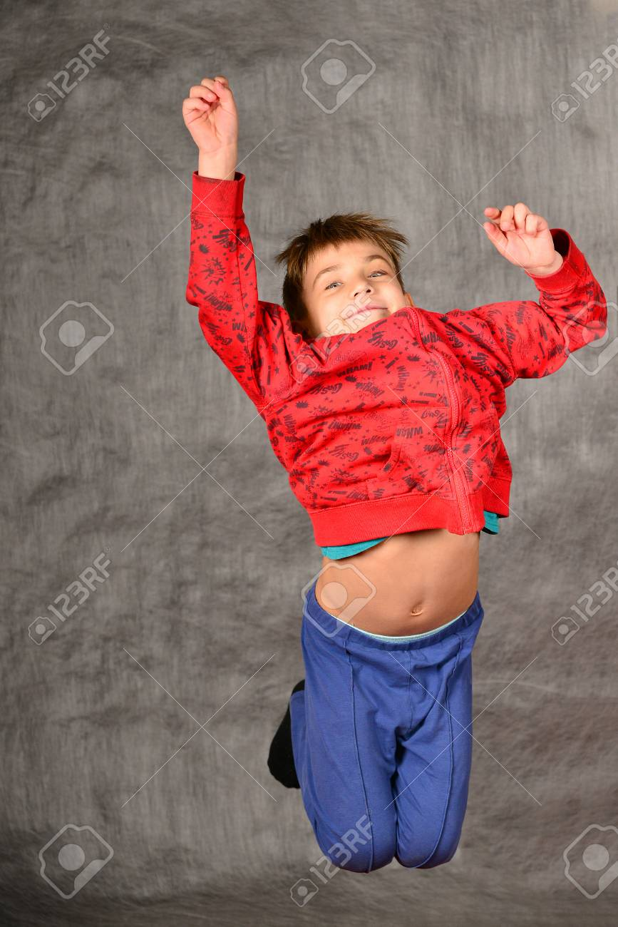 A boy in a red sweater and blue pants jumps and holds his hand up in the  studio on a gray background