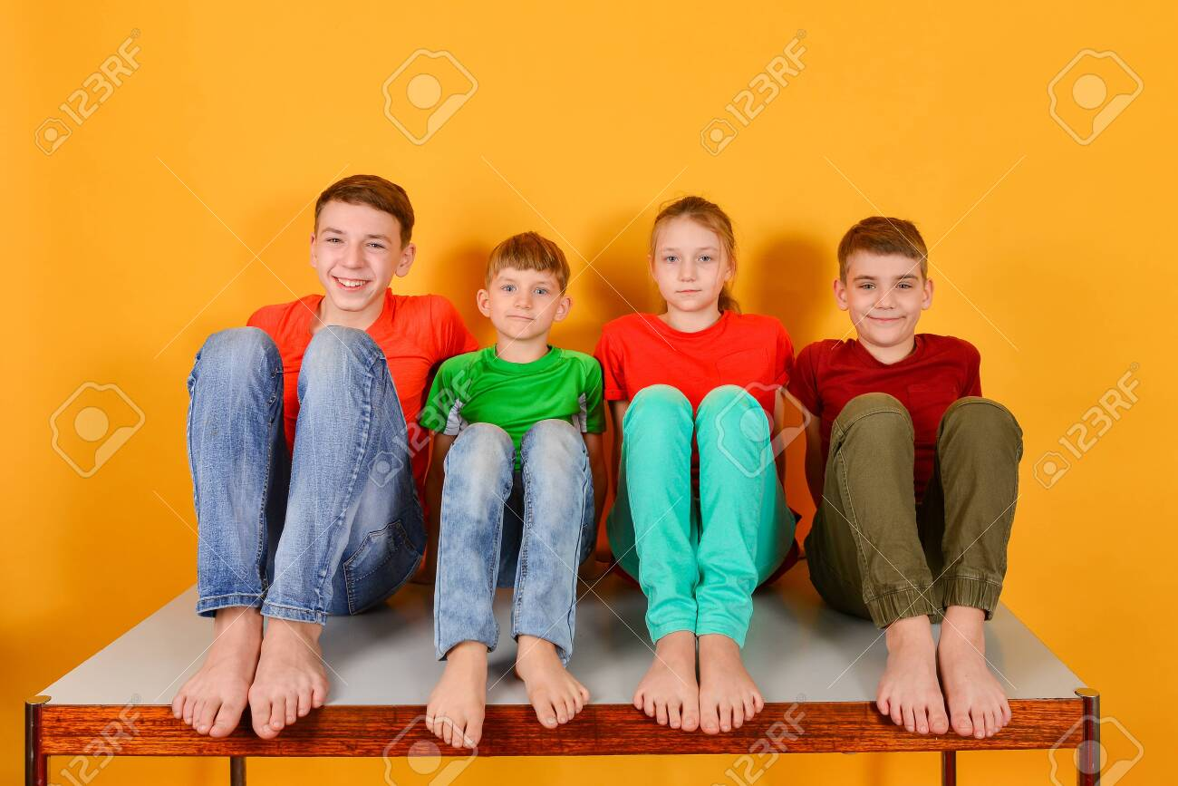 Four children squatting barefoot, a bright colorful juicy photo of teenagers sitting in colored clothes - 140307154