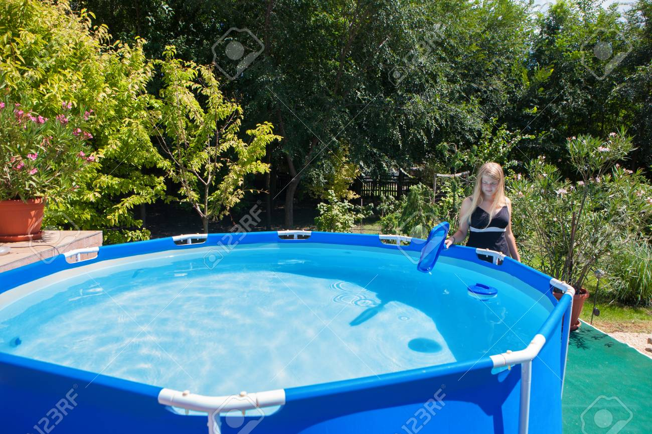 Beautiful young woman wearing one-piece swimsuit cleaning a..