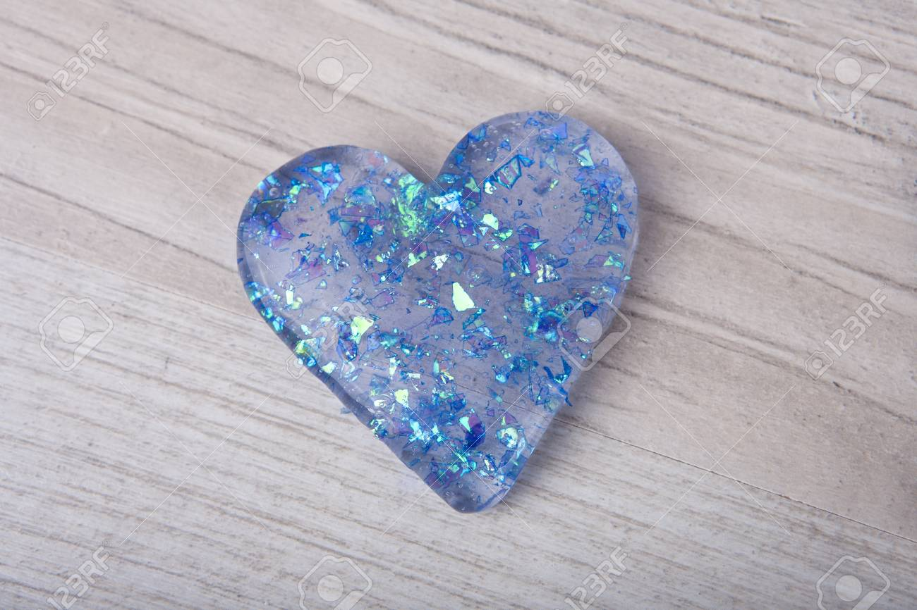 Heart shape blue glitter slime on a wooden table