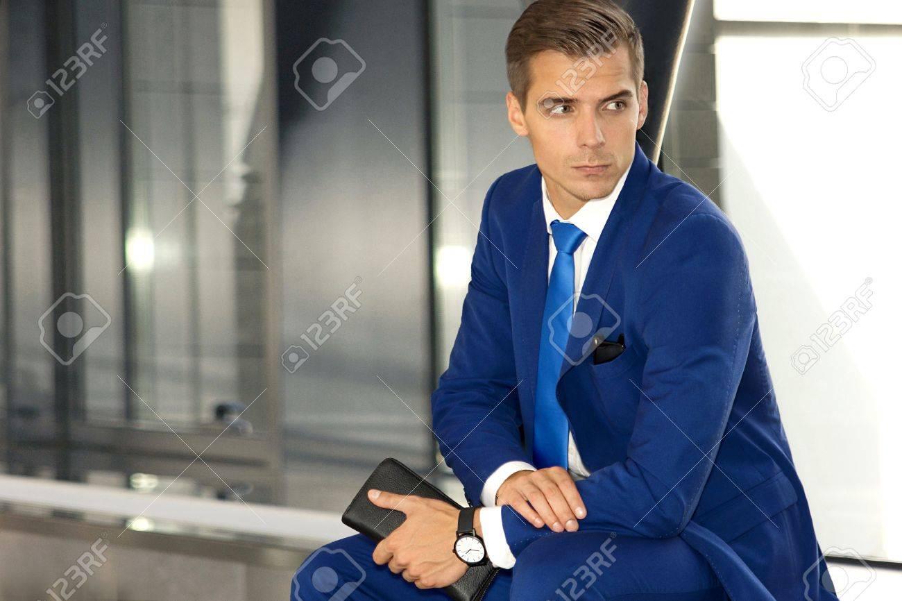 b5a719c5f1979 Foto de archivo - Un hombre con un traje azul está sentado en un edificio  moderno