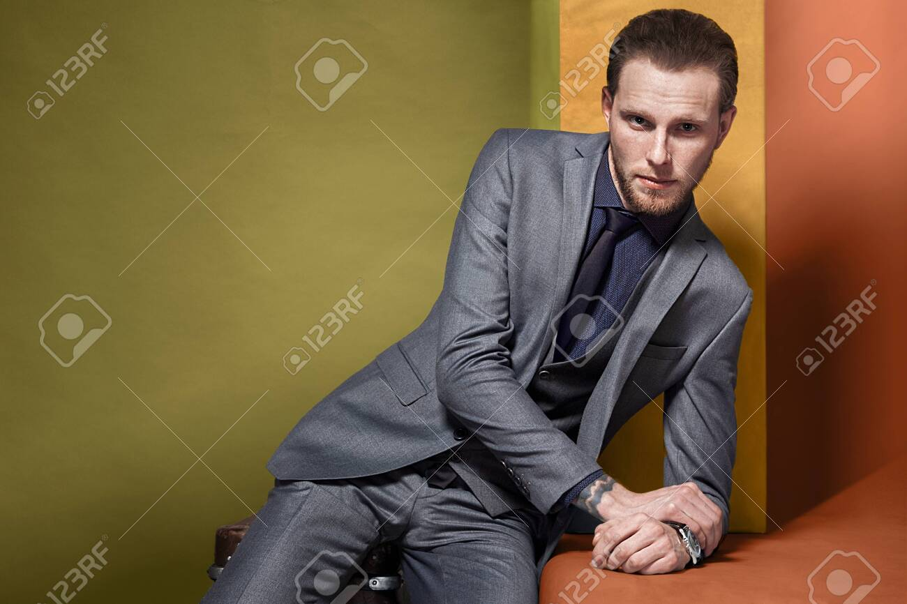 man in a gray suit on a bright orange green swampy background - 133105898