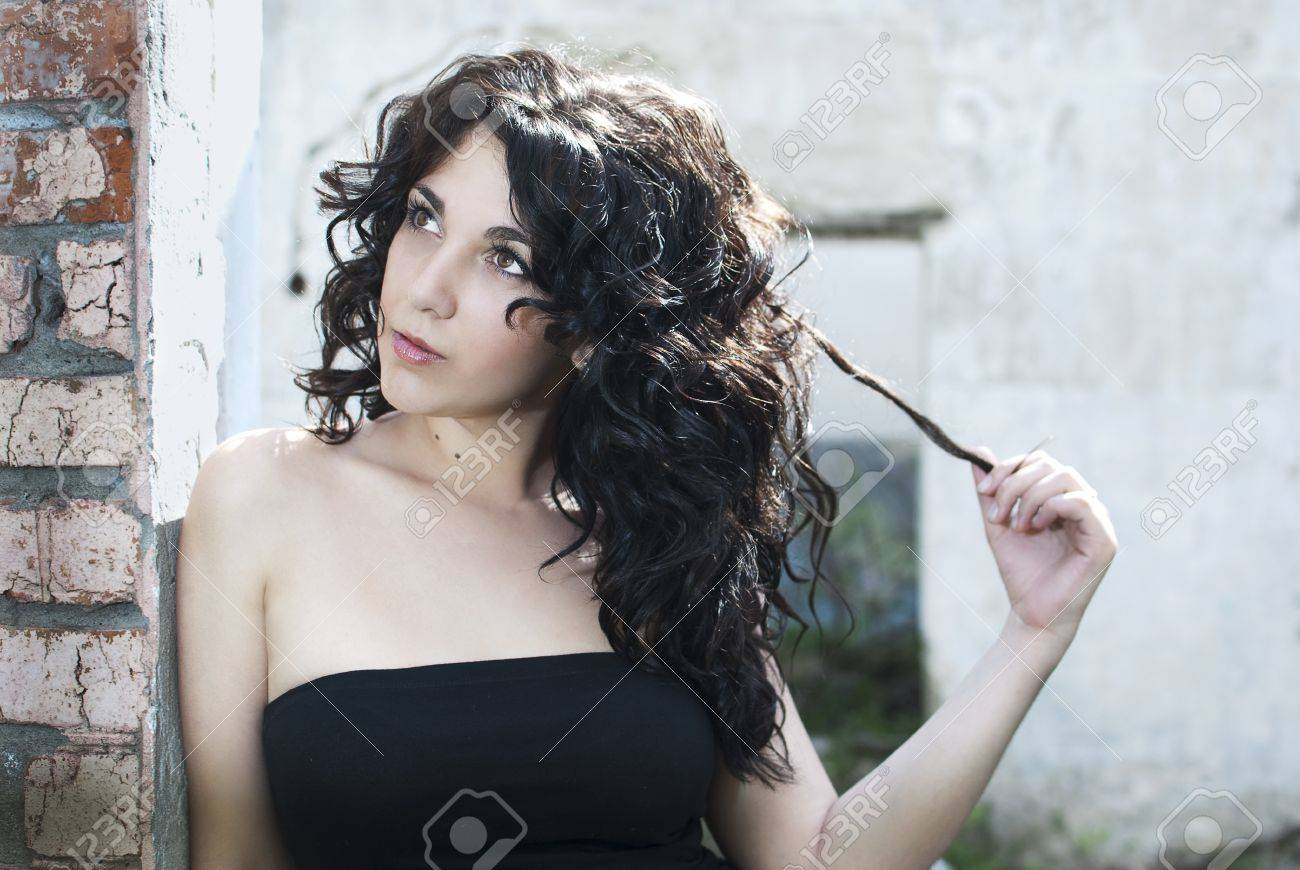 Portrait of a beautiful girl in close-up on a background of ruins. Looks away, turns the hair. Stock Photo - 9598308