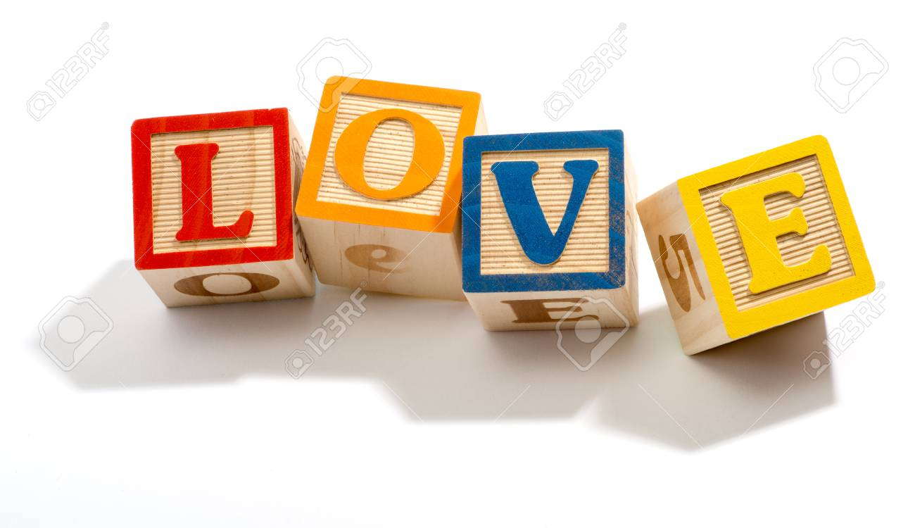 love in colored wooden letter blocks in close up isolated on a white background stock