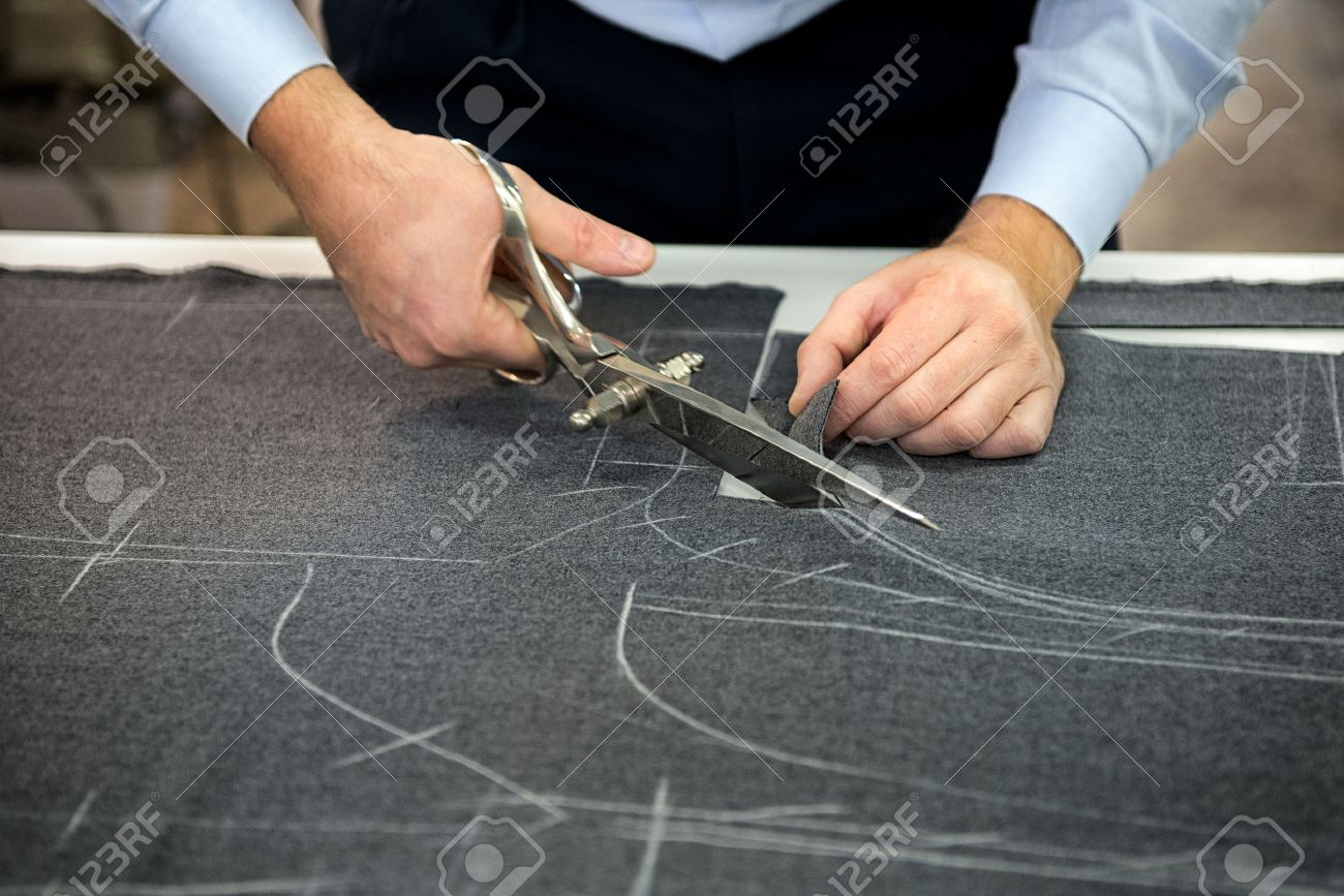 tailor cutting fabric using large scissors or shears as he follows