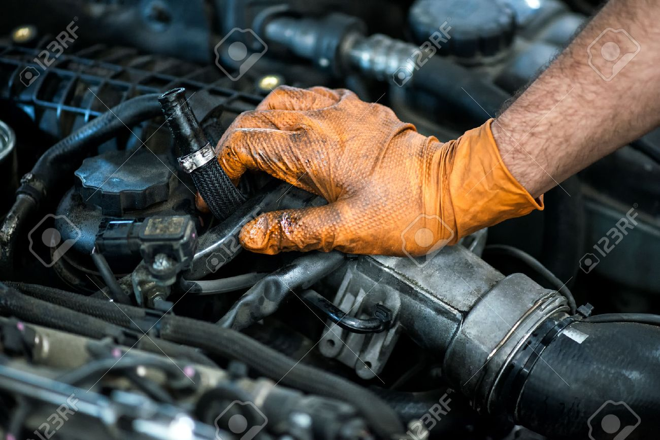 Hand of a mechanic in an oil covered glove resting on a car engine in a close up view conceptual of maintenance in a workshop, or of a career as a mechanic - 52665246