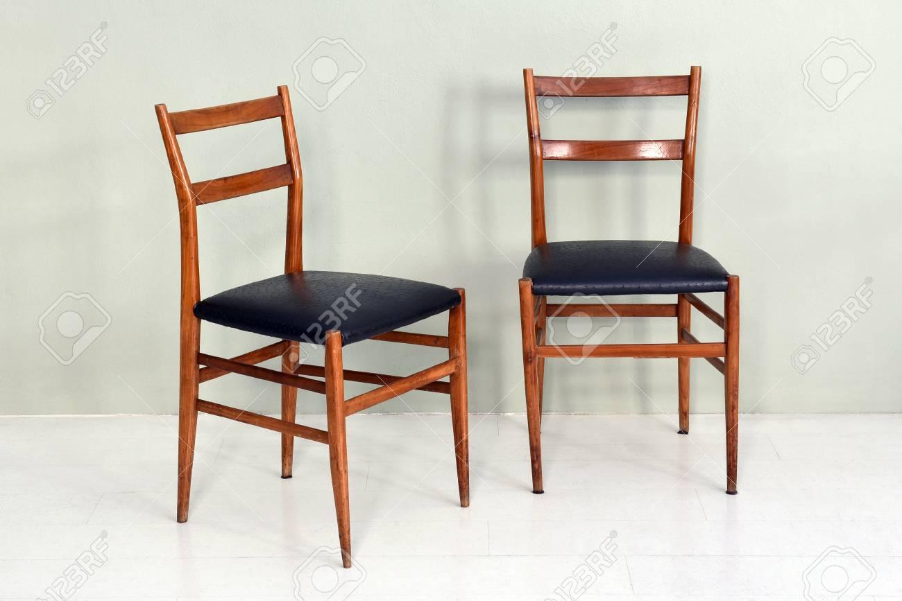 Style De Chaises Anciennes nature morte de paire de chaises de cuisine anciennes d'époque avec pieds  et bases en bois et sièges rembourrés noirs dans une pièce à fond uni