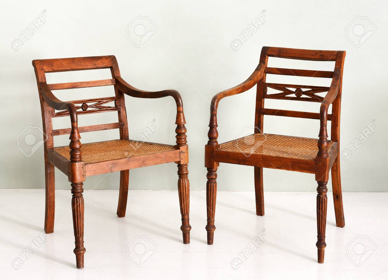 Stock Photo   Two Vintage Colonial Style Wooden Armchairs With Spindle Form  Legs And Wicker Or Cane Seats, Possibly Servers From A Dining Set