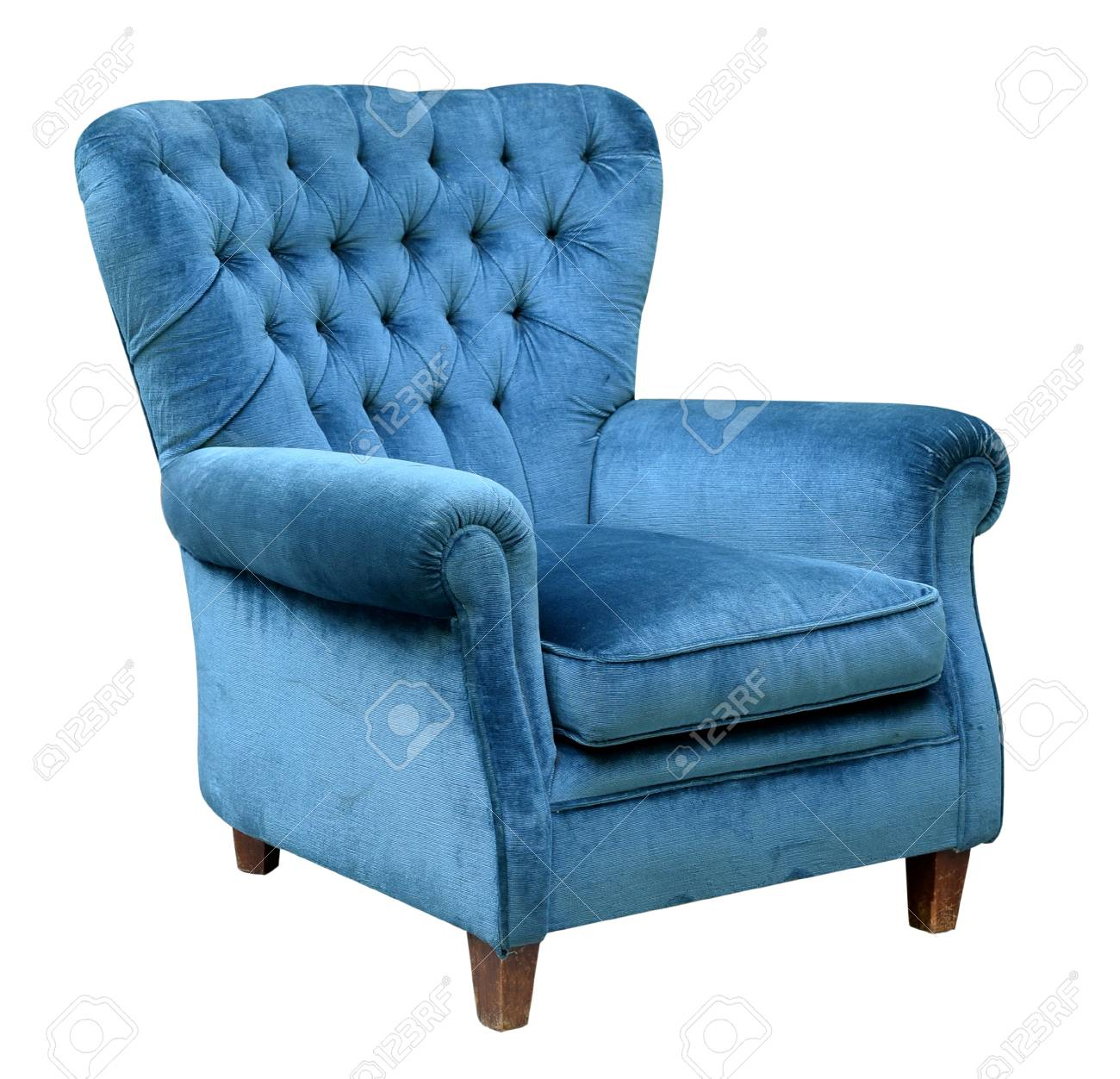 Stock Photo   Upholstered Blue Velvet Armchair With A Retro High Button  Back Design Isolated On White In A Three Quarter View