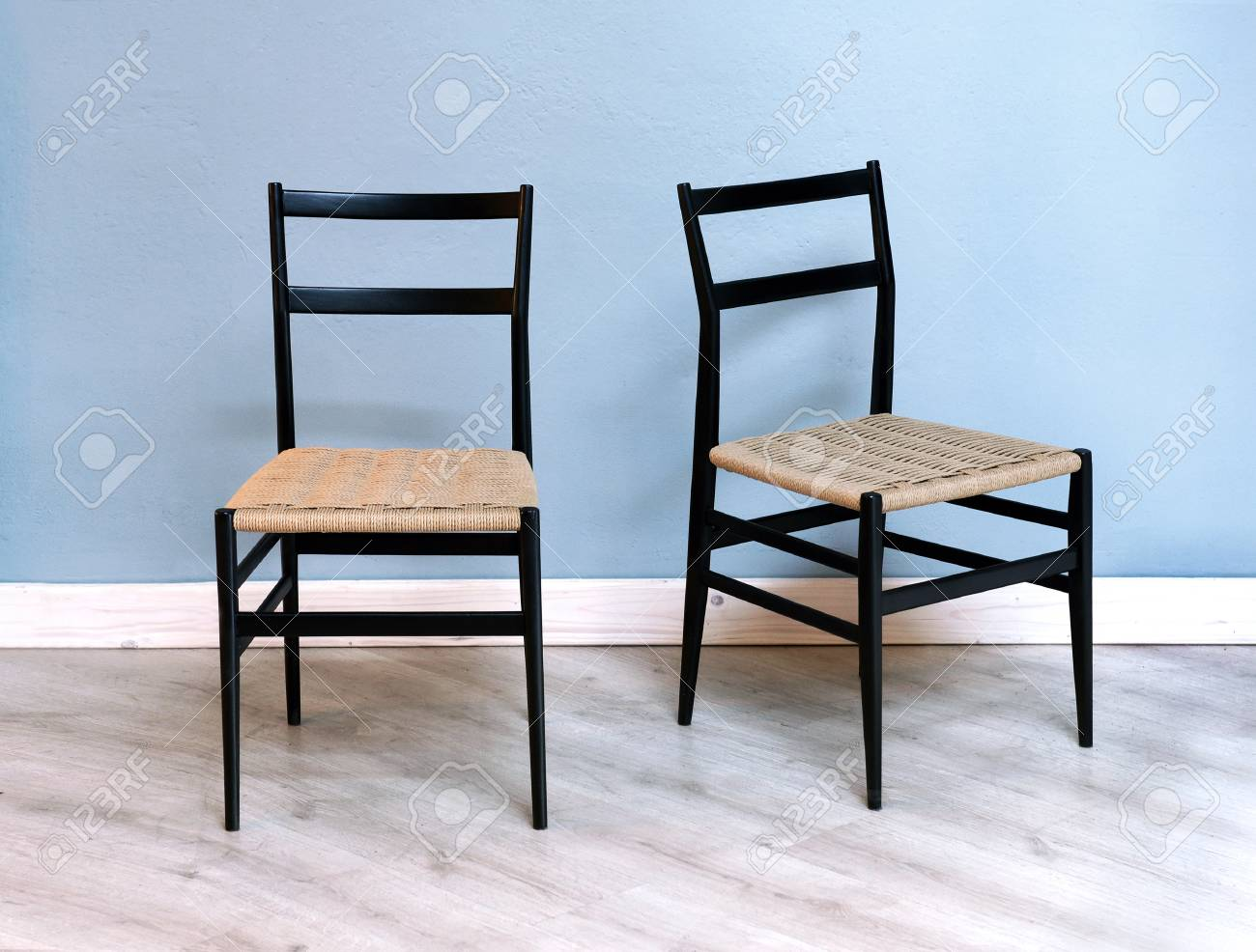 Two simple black kitchen or dining chairs with woven wicker seats..